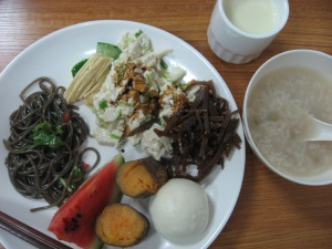 "The best breakfast. Tofu skin, fresh tofu with soy sauce, mystery pickle, bean bun, watermelon, chilli and garlic konyakku noodles. With plain congee and warm, fresh ""bean milk"""